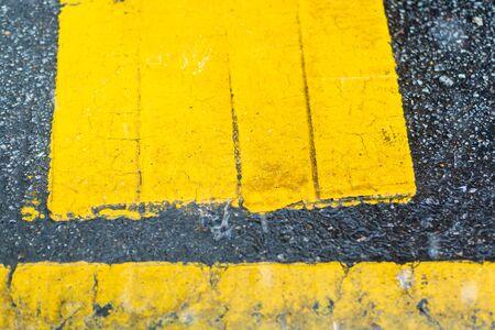 Road markings in yellow paint on black asphalt.