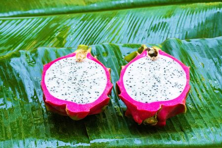 Ripe dragon fruit on a wet green leaf. Vitamins, fruits, healthy foods.