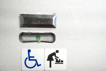 A sign in the toilet of an airplane, meaning that the toilet is equipped for disabled people. And it has a changing table.
