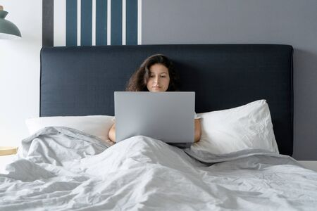 Beautiful brunette girl in bed with a laptop. Work from morning to late night. Electronic gadgets before bedtime or in the morning Reklamní fotografie