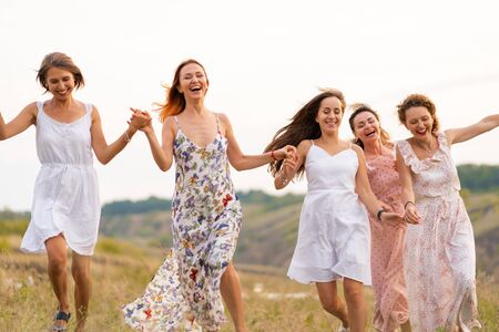 The company of cheerful female friends have a great time together on a picnic in a picturesque place overlooking the green hills. Girls in white dresses dancing in the field.