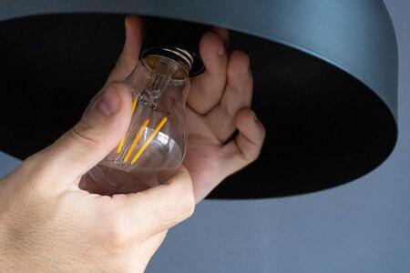 Close-up. A hand changes a light bulb in a stylish loft lamp. Spiral filament lamp. Modern interior decor