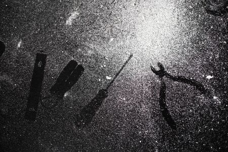 Traces of tools on a black table dusted with white dust. Archivio Fotografico