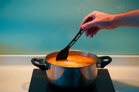Cooking soup in a pan on an induction stove. Foto de archivo