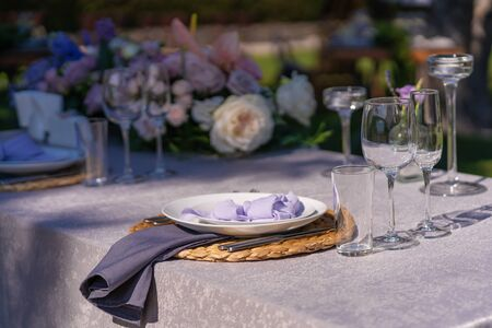 The festive table is served and decorated with fresh flowers. Details of festive decorations with fresh flowers.
