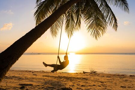 The guy enjoys the sunset riding on a swing on the ptropical beach. Silhouettes of a guy on a swing hanging on a palm tree, watching the sunset in the water Banco de Imagens