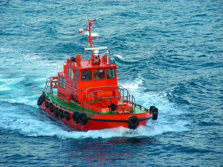 Rotes Schiffsschleppersegeln im blauen Meer, das die Wellen bricht. Editorial