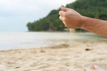 Play with sand on the beach. Sand is poured from the hands, against the backdrop of a tropical island