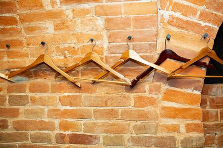 Pub room decor, wooden clothes hangers hanging on a red brick arched wall.