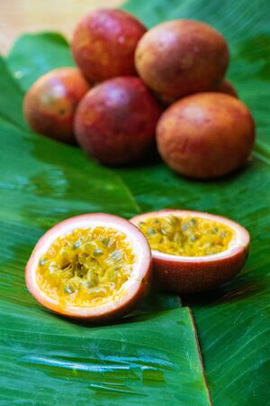 Ripe passion fruit, on a wet banana leaf. Vitamins, fruits, healthy foods.