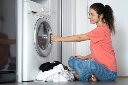 A girl loads dirty laundry into a washing machine while sitting on the floor in an apartment. Laundry day, housework.