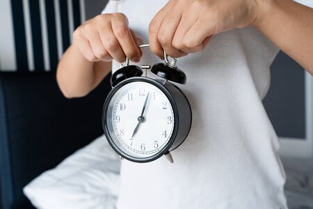A guy in a white T-shirt is holding a stylish black alarm clock with a bell. On the alarm clock, the beginning of the eighth. Time to get up
