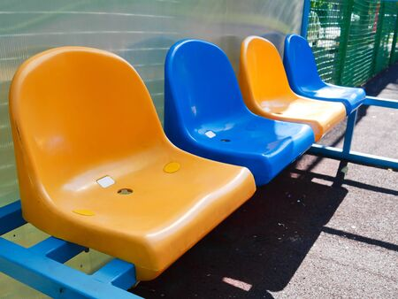 A row of plastic seats for waiting on the tennis court