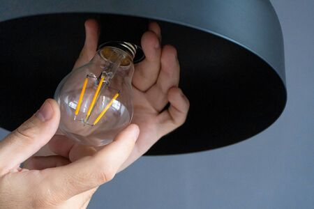 Close-up. A hand changes a light bulb in a stylish loft lamp. Spiral filament lamp. Modern interior decor