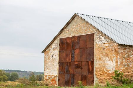 Old red brick hangar with huge gates made of rusted metal. Warehouse for rural products.