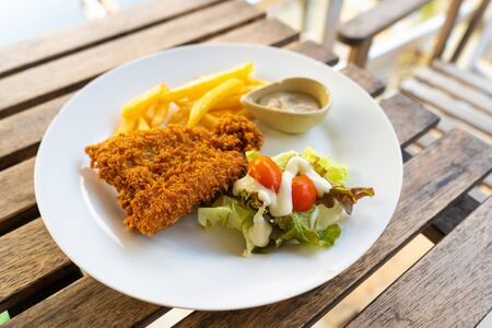 Dish Fish in batter with french fries. Fish on a plate with potatoes and salad in a summer cafe