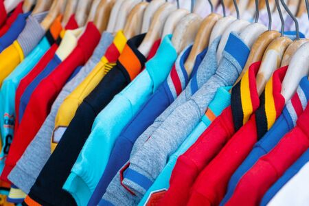 Multi-colored t-shirts on a hanger. Clothing store. Фото со стока