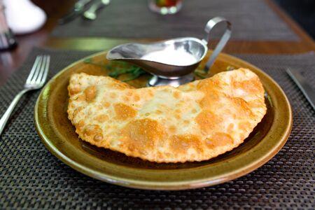 Juicy cheburek with sour cream. Crimean Tatar cuisine. Meat pie