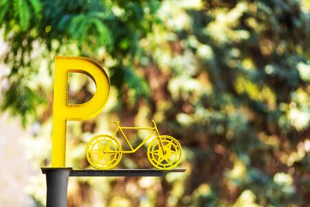 Designation of parking for bicycles. Big yellow letter P on a pillar. Standard-Bild - 147819767