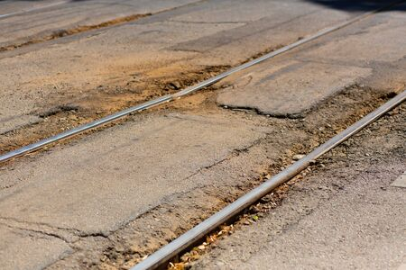 broken asphalt road near tram track close up.