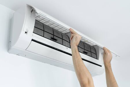 The guy cleans the filter of the home air conditioner from dust. Very dirty air conditioner filter. Climate equipment care
