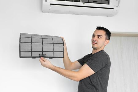 The guy cleans the filter of the home air conditioner from dust. Very dirty air conditioner filter. Climate equipment care Foto de archivo