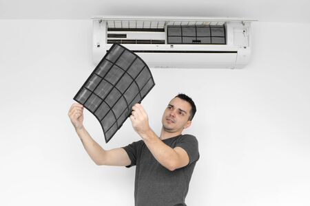 The guy cleans the filter of the home air conditioner from dust. The guy snayed a very dirty air conditioning filter. and examines it in his hands. Climate equipment care Foto de archivo