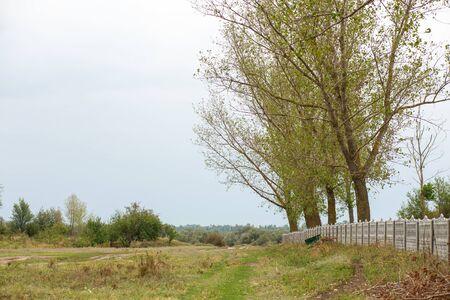 A fence along an empty field. Rural landscape