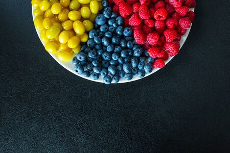 View from above. A mix of yellow, red and blue berries in a white grater. Triangle separation. Summer mix of fruits. Berry layout. Stockfoto