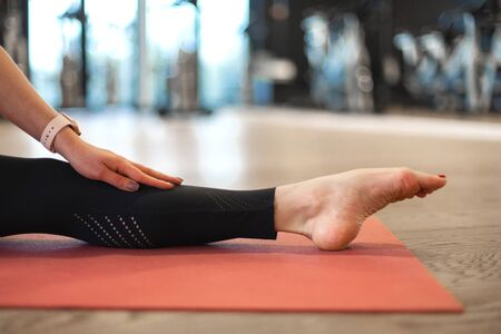 Portrait of young woman in the gym sitting on the splits. Fit and wellness lifestyle.