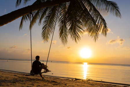 The guy enjoys the sunset riding on a swing on the ptropical beach. Silhouettes of a guy on a swing hanging on a palm tree, watching the sunset in the water