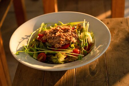 Restaurant serving food. Tuna salad in a plate on a table in a summer cafe.