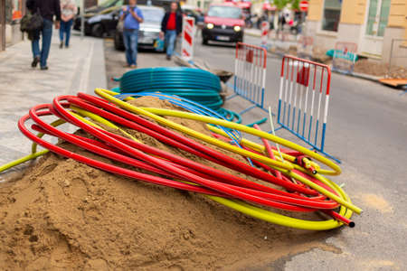 Repair work on city streets. Laying cable routes. Coils of plastic casings.