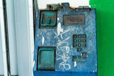 Old broken payphone. Traces of poverty and devastation Фото со стока