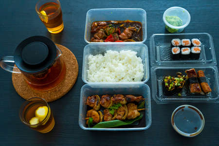 Asian food, sushi, rolls, rice and chicken skewers. Food in disposable dishes. Order Asian Food at Home. Stok Fotoğraf