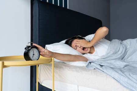 The girl turns off the annoying alarm clock to continue sleeping. Get some more sleep. It?s a hard morning. Time to wake up