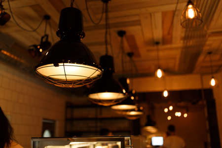 Stylish lighting lamps over a bar counter in a loft hookah bar. Imagens