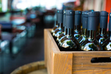 A wooden box filled with bottles of wine. Bank party celebration in an open-air restaurant.