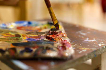 Close-up of an easel with paints, the artist paints a brush. Painting a picture