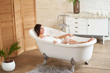 A attractive girl relaxes in the bathroom and rests against the backdrop of a beautiful light interior. Spa treatments for beauty and health with skin care.