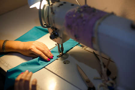 Girl seamstress in the light of a desk lamp stitching a blue cloth on a sewing machine.