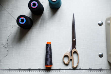 top view of scissors and skeins of thread on a white table with markings. Sewing industry. Manufacturing of clothes.