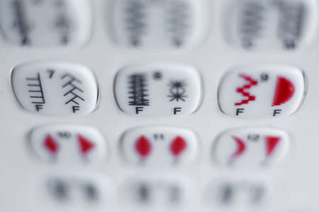 A set of buttons to select the type of stitching on the sewing machine. Sewing industry. Фото со стока