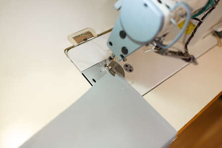 Close-up of a sewing machine with light on and item of cloth. workplace tailor. sewing industry. Фото со стока