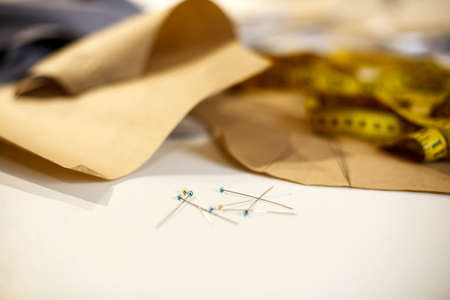 Closeup set on needles, centimeter and paper pattern on tailor desktop. Tailor industry concept.