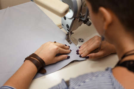 Workplace seamstress. Tailoring industry. Girl sews on the sewing machine. Factory clothing.