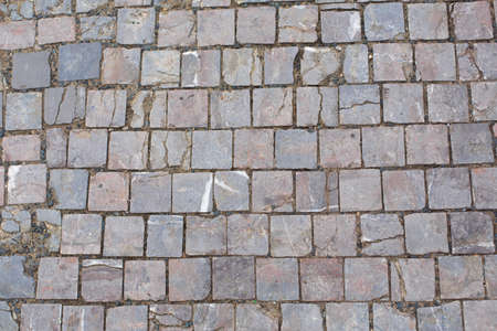 Texture of old broken stone paving stones.
