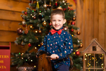 Children's joyful memories of Christmas holidays. Santa gave a little boy a swing horse.