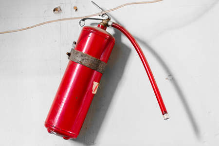 A red balloon fire extinguisher hangs on a white wall. Fire safety in the building. Banque d'images