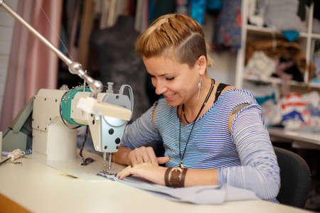 Young female blonde dressmaker works on sewing machine. dress manufacturing industry.